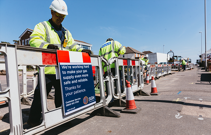 An engineer placing a sign on some roadworks barriers. The sign reads: We're working hard to make your gas supply even more safe and reliable. Thanks for your patience.