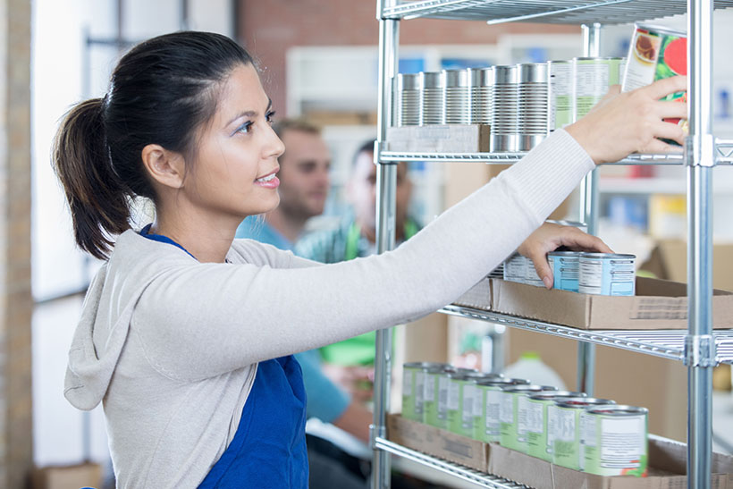 Foodbank manager stacking shelves