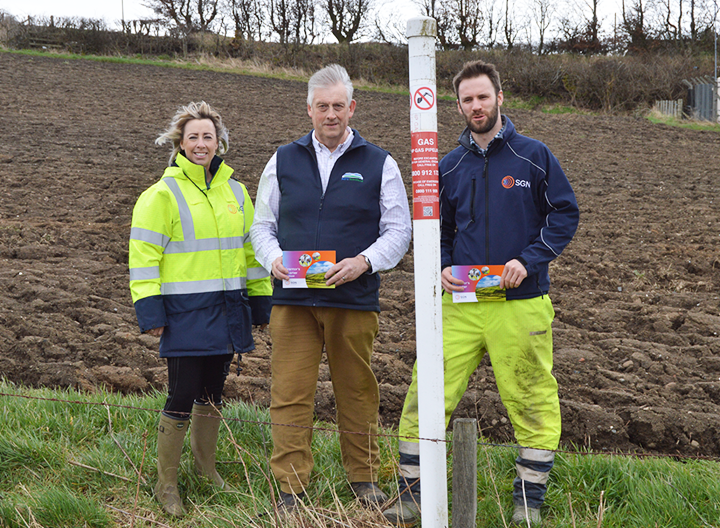 SGN colleagues with NFU Scotland partners standing in field next to pipeline location marker