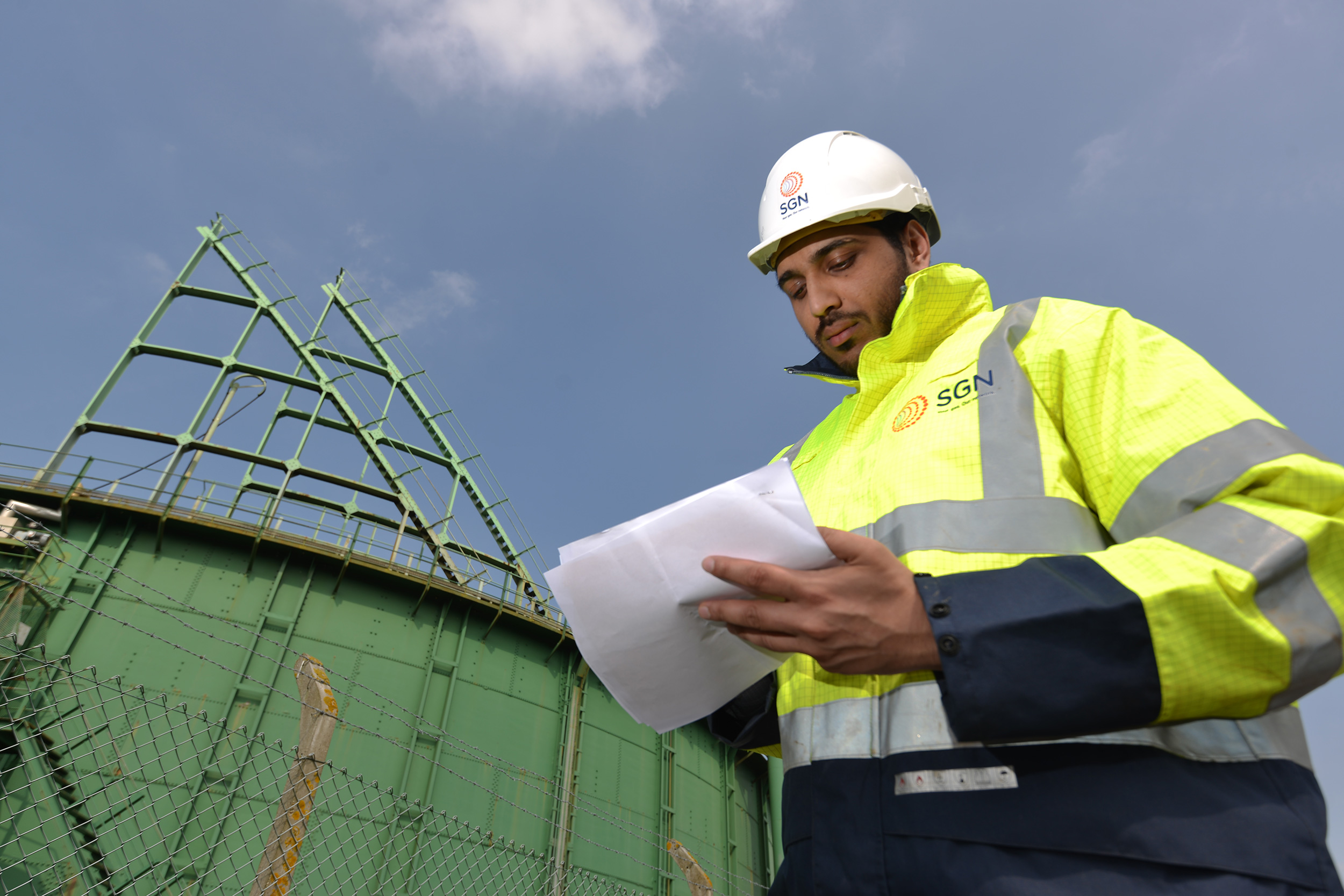 A SGN engineer wearing a high-visibility jacket and hardhat and holding a piece of paper, standing in front of a gas holder