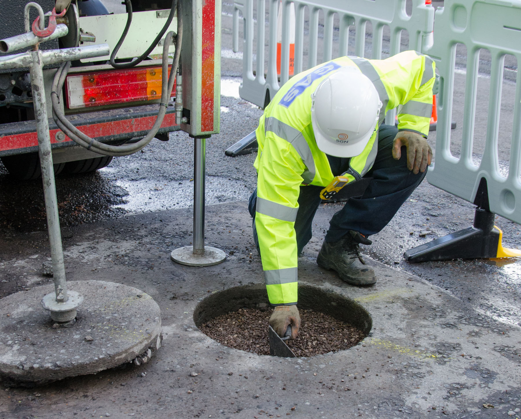 Gas engineer restoring road surface following core and vac