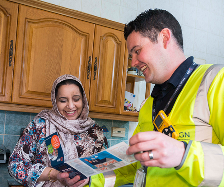 A SGN engineer shows a leaflet to a customer