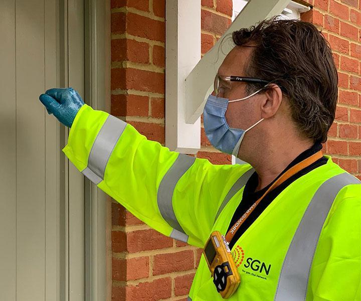 A SGN engineer knocking on a customer's door.  The engineer is wearing a high-viz jacket, a face mask and disposable gloves.