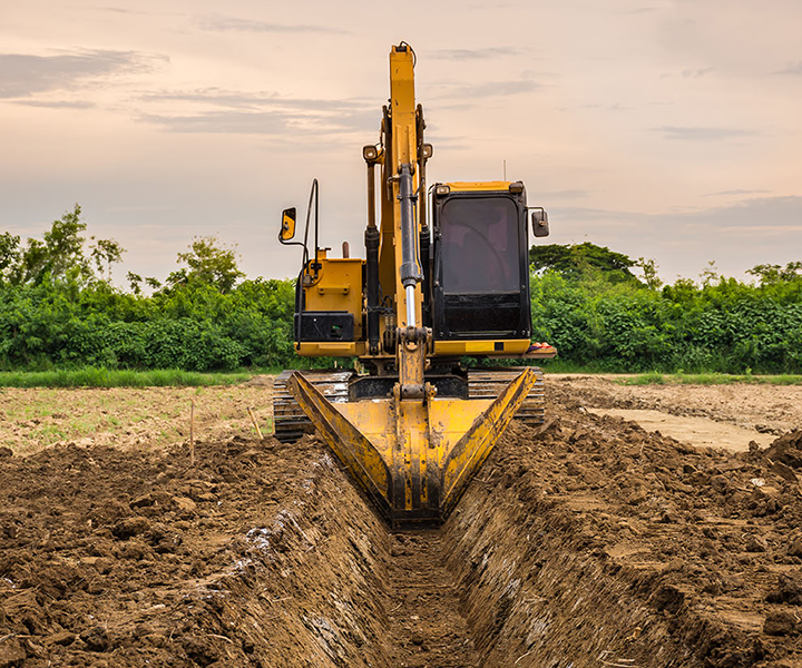 A yellow excavator digging a trench in a field