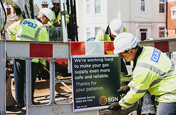 "Gas engineers working in the street. The sign says ""we're working hard to make your gas supply safe and reliable. Thanks for your patience."""